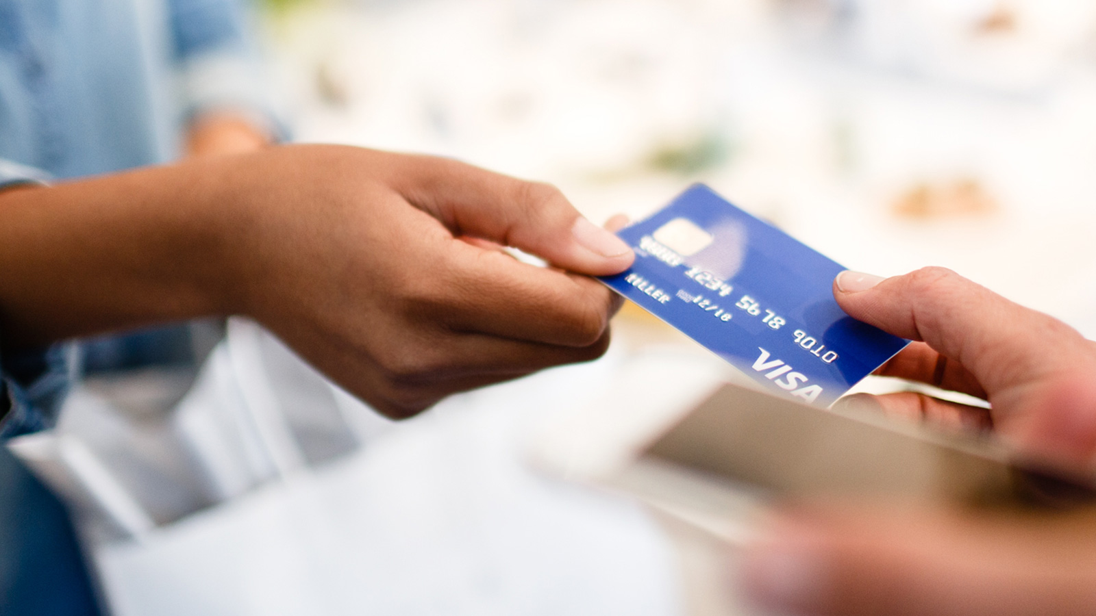 Woman handing Visa card to clerk for purchase.